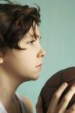Garçon d'adolescent avec visage de boule de basket-ball le demi image stock