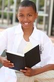 Garçon d'adolescent d'Afro-américain affichant un livre Photos stock