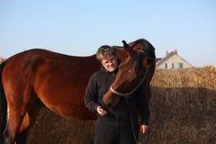 Garçon d'adolescent dans le noir étreignant le cheval brun Photo stock