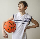 Garçon d'adolescent dans une chemise blanche avec une boule pour le basket-ball photographie stock