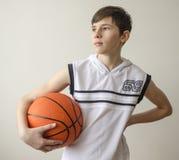 Garçon d'adolescent dans une chemise blanche avec une boule pour le basket-ball photo stock