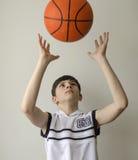 Garçon d'adolescent dans une chemise blanche avec une boule pour le basket-ball photo libre de droits