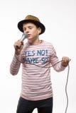 Garçon d'adolescent de brune de chanteur dans un débardeur rose dans le chapeau d'or avec un microphone Photographie stock libre de droits