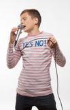 Garçon d'adolescent de brune de chanteur dans un pullover rose avec un microphone Images libres de droits