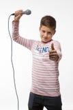 Garçon d'adolescent de brune de chanteur dans un pullover rose avec un microphone Photos stock