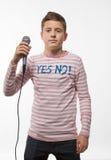 Garçon d'adolescent de brune de chanteur dans un pullover rose avec un microphone Image stock