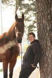 Garçon d'adolescent et cheval brun se tenant près de l'arbre Photos stock