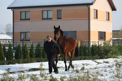 Garçon d'adolescent et cheval de baie descendant en courant la rue de village Image libre de droits