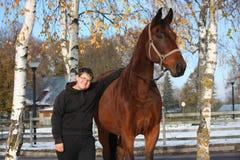 Garçon d'adolescent et portrait brun de cheval en automne Image libre de droits