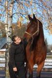 Garçon d'adolescent et portrait brun de cheval en automne Photographie stock