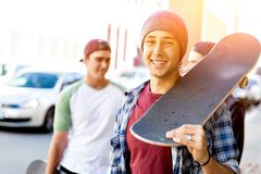 Garçon d'adolescent marchant à la rue avec sa planche à roulettes Photos stock