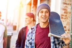 Garçon d'adolescent marchant à la rue avec sa planche à roulettes Photographie stock libre de droits