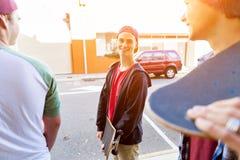Garçon d'adolescent marchant à la rue avec sa planche à roulettes Image libre de droits