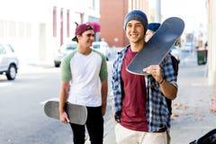 Garçon d'adolescent marchant à la rue avec sa planche à roulettes Images libres de droits