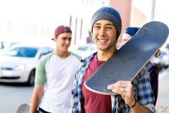 Garçon d'adolescent marchant à la rue avec sa planche à roulettes Photos libres de droits