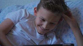Garçon d'adolescent reposant avec le comprimé, souriant, écran tactile clips vidéos