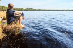 Garçon d'adolescent s'asseyant près du lac de forêt Photo stock