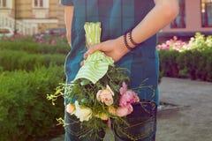 Garçon d'adolescent tenant le bouquet des fleurs derrière le sien de retour Surprise, cadeau, actuel Photo stock