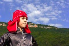 Garçon d'adyghe de portrait dans la robe nationale circassienne sur un fond des montagnes et du ciel bleu sur le festival ethniqu Photos stock