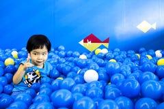 Garçon d'ASEAN comptant la boule dans la salle de jeux complètement des boules Photos libres de droits