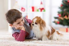 Garçon d'enfant avec le chien se trouvant à l'arbre de Noël sur le plancher photographie stock