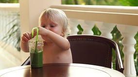 Garçon d'enfant buvant et jouant avec un smoothie sain de légume-fruit - consommation saine, vegan, végétarien, aliment biologiqu banque de vidéos