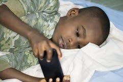 Garçon d'enfant dans le lit avec le smartphone photo stock