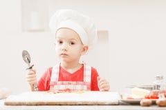 Garçon d'enfant dans les tabliers et des chapeaux du chef coupant une pizza image stock