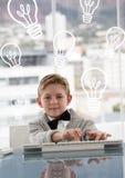 Garçon d'enfant de bureau à l'aide de l'ordinateur sur le fond avec des icônes d'ampoules Image libre de droits