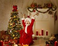Garçon d'enfant de Noël en Santa Hat And Bag, enfant dans la chambre décorée Photos stock