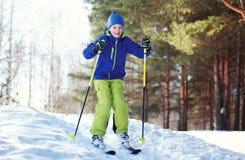 Garçon d'enfant de skieur d'hiver dans les vêtements de sport skiant au-dessus de la neige Images stock