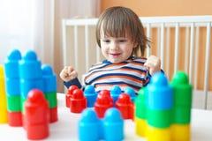 Garçon d'enfant en bas âge (2 ans) jouant des blocs de plastique à la maison Images stock