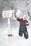 Garçon d'enfant en bas âge avec le renne dans la neige photos stock