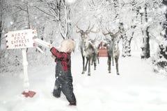 Garçon d'enfant en bas âge avec le renne dans la neige image libre de droits