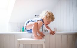 Garçon d'enfant en bas âge dans une situation dangereuse dans la salle de bains photo stock