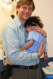 Garçon d'enfant en bas âge de fixation de père dans l'ER Image stock