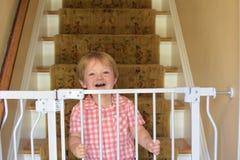 Garçon d'enfant en bas âge derrière des portes de bébé Image libre de droits