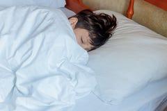 Garçon d'enfant en bas âge dormant dans le lit à la maison, Image libre de droits
