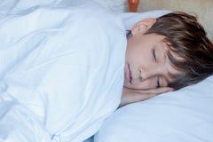 Garçon d'enfant en bas âge dormant dans le lit à la maison, Image stock