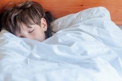 Garçon d'enfant en bas âge dormant dans le lit à la maison, Photo stock