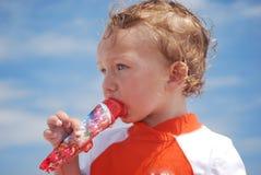 Garçon d'enfant en bas âge mangeant un bruit de glace à l'extérieur sur la plage Photographie stock libre de droits