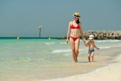 Garçon d'enfant en bas âge marchant sur la plage avec la mère Images stock
