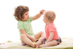 Garçon d'enfant en bas âge montrant un oeuf à un bébé Photo libre de droits