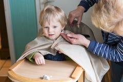 Garçon d'enfant en bas âge obtenant sa première coupure de cheveu Images libres de droits