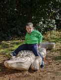 Garçon d'enfant en bas âge s'asseyant sur une statue de crocodile Image stock