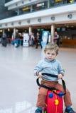 Garçon d'enfant en bas âge s'asseyant sur une valise à l'aéroport Photographie stock libre de droits