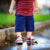Garçon d'enfant en bas âge se tenant dans un magma Photo stock