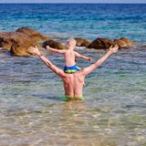 Garçon d'enfant en bas âge sur les épaules du père à la plage photographie stock