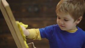 Garçon d'enfant essuyant le tableau sur le fond en bois, plan rapproché Travail de garçon Garçon d'enfant avec le visage concentr banque de vidéos