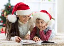 Garçon d'enfant et son livre de lecture de maman à Noël Image stock